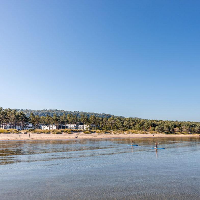 Bild tagen från hav mot hotell och konferensanläggning vid strand.