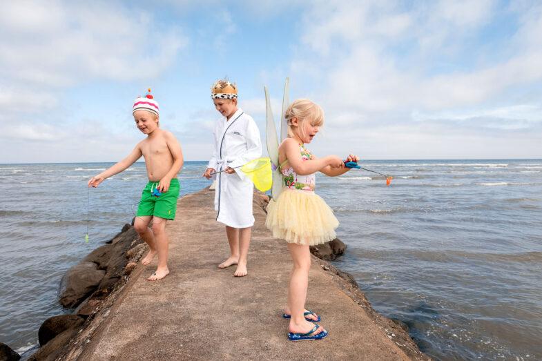Barn fiskar krabbor på stenbrygga vid havet.
