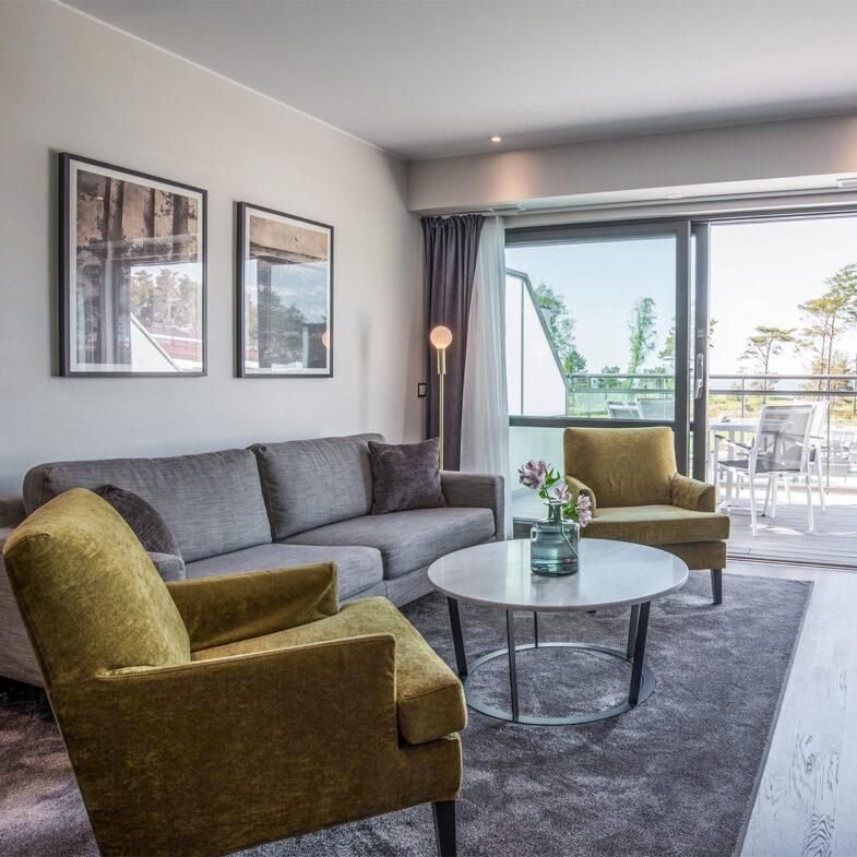Vardagsrum i hotellrum med soffa och fåtöljer