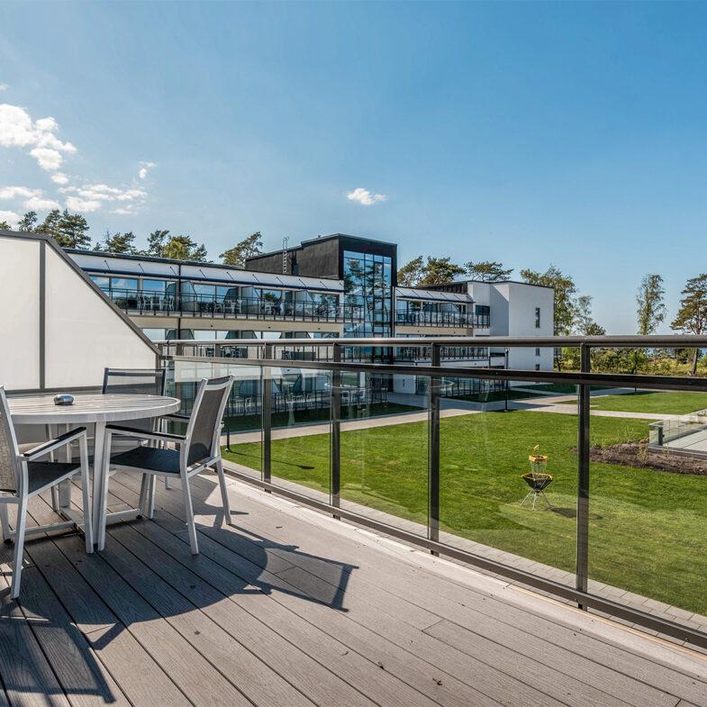 Balkong från hotellrum med utsikt över hotellbyggnad, innergård och hav