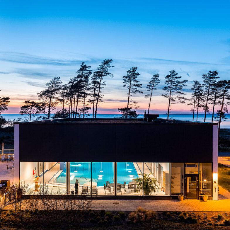 Poolbyggnad på innergård med utsikt över hav i skymning.