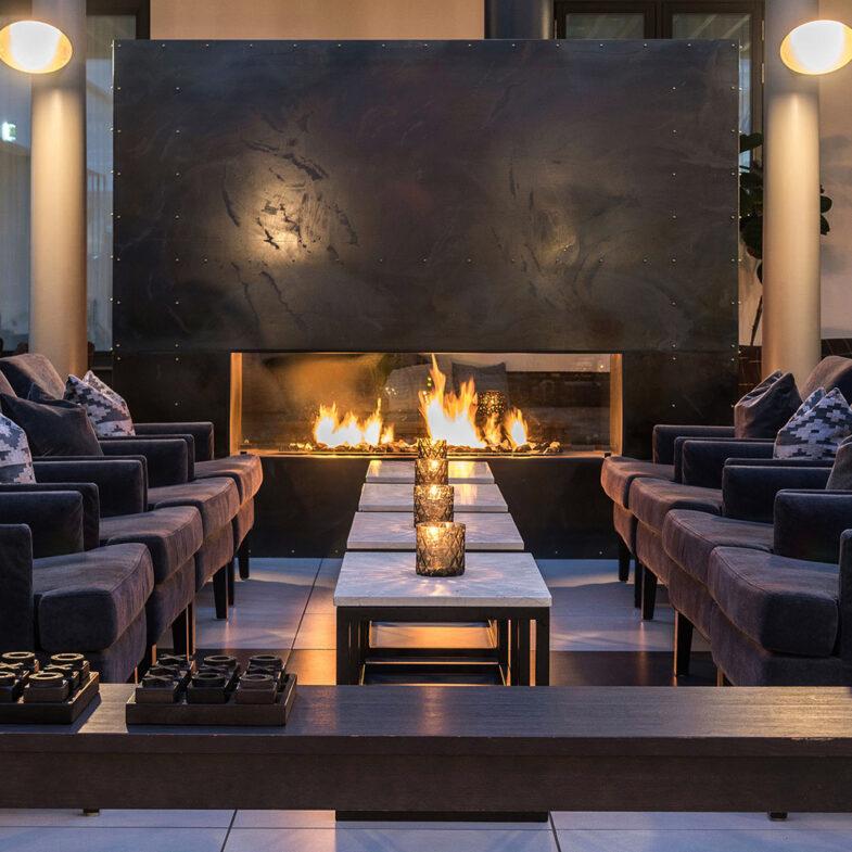 Brasa lyser upp lounge med fåtöljer och marmorbord.