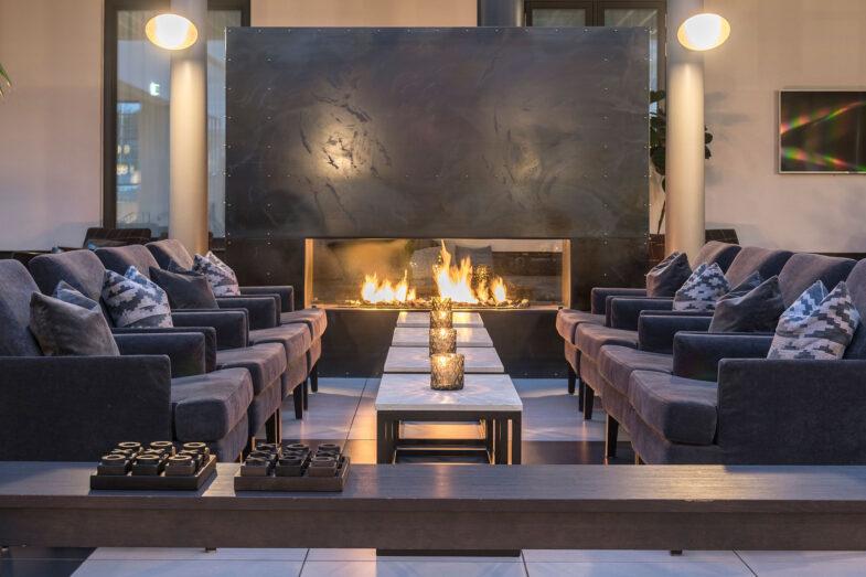 Brasa lyser upp sittgrupp med fåtöljer i lounge.