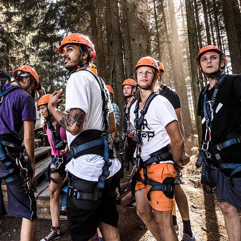 En grupp personer med klättringsutrustning i skog