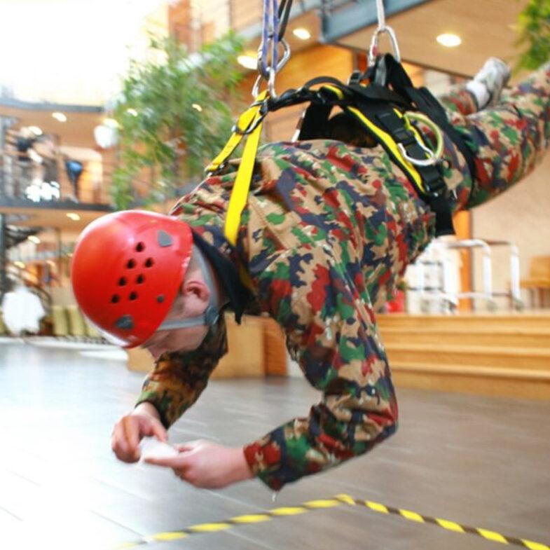 Man med klättringsutrustning hänger från tak