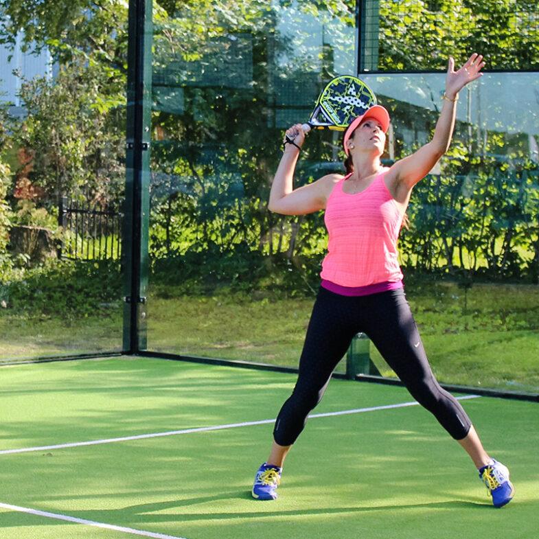 Kvinna spelar padel på bana