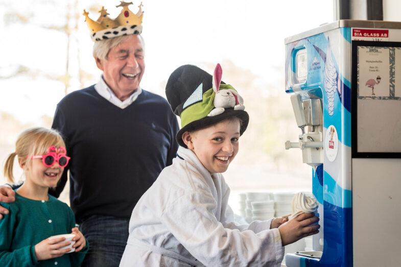 Barn i badrock tar mjukglass från glassmaskin.