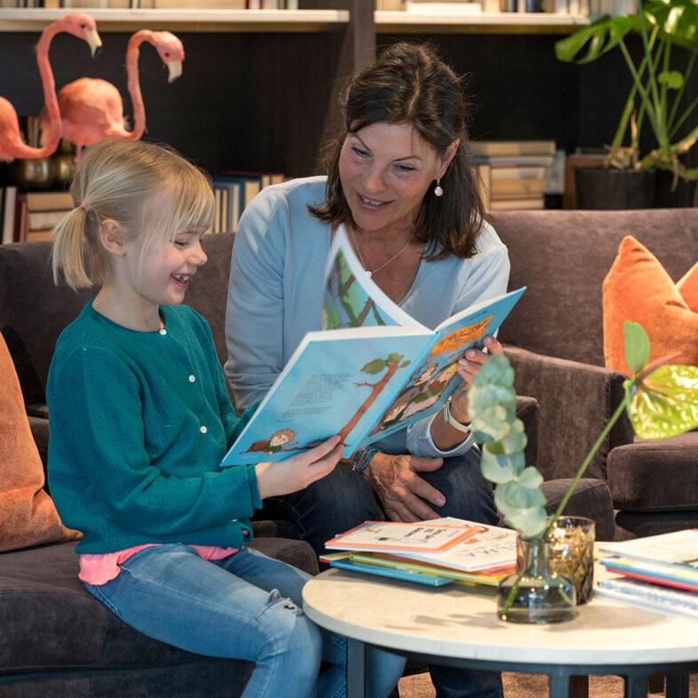 Kvinna och flicka läser barnbok i lounge.