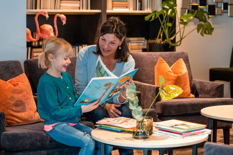 Barn och kvinna läser barnbok i lounge.