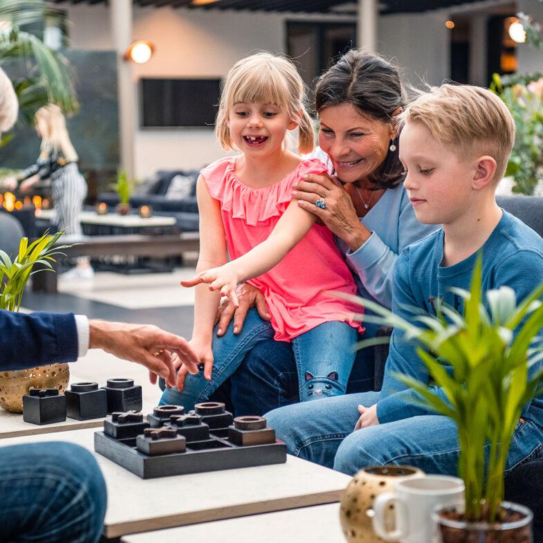 Kvinna och barn spelar sällskapsspel i lounge.