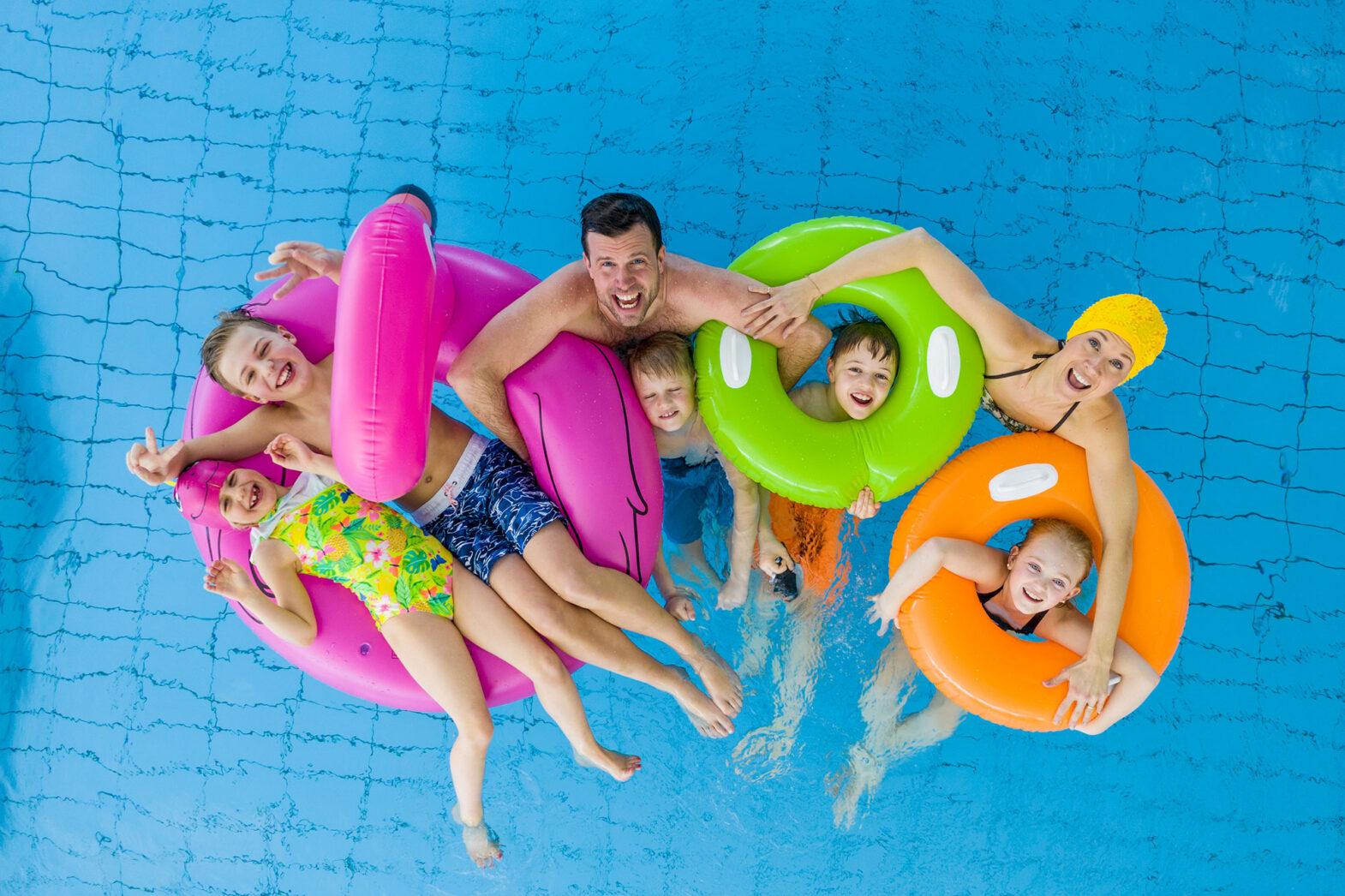 Familj badar i pool tillsammans.