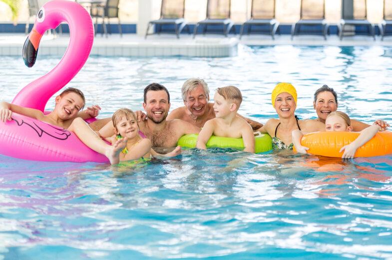 Stor familj badar tillsammans i poolhus på Hotel Riviera Strand.