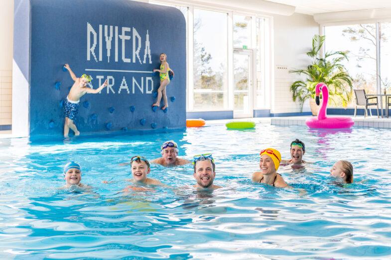 Stor familj badar tillsammans i inomhuspoolen på Hotel Riviera Strand.