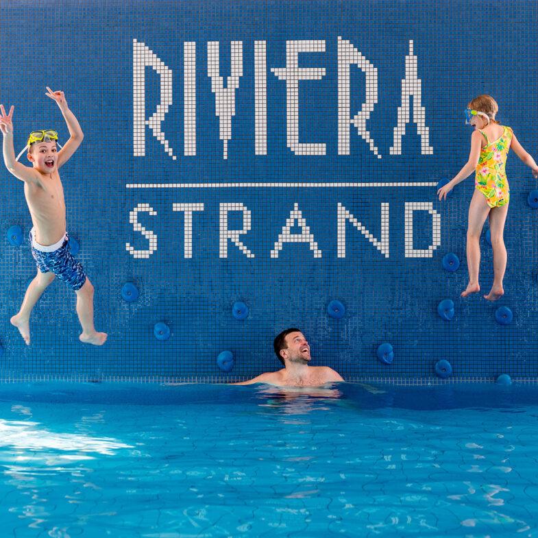 Barn hoppar från klättervägg ner i poolen.
