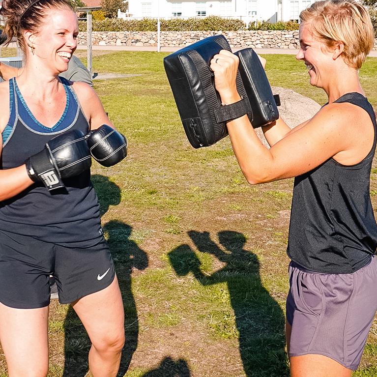 Två personer tränar boxning utomhus i solen