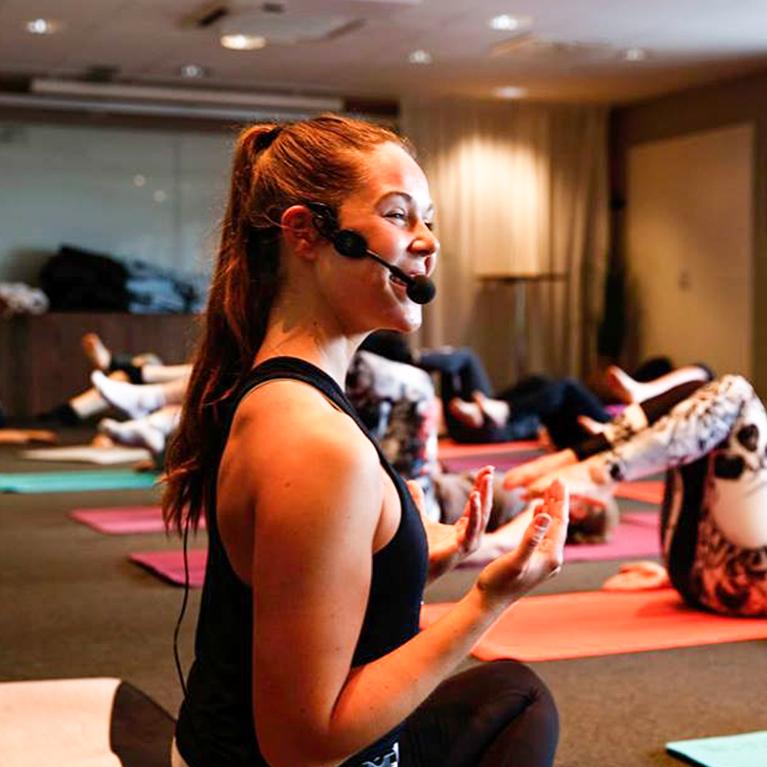 kvinna instruerar yoga inför grupp