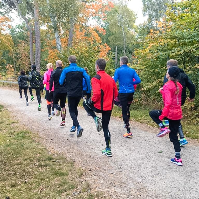Grupp personer tränar på grusväg