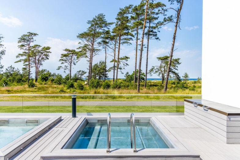 Japansk pool på terrass med hav och skog i bakgrunden