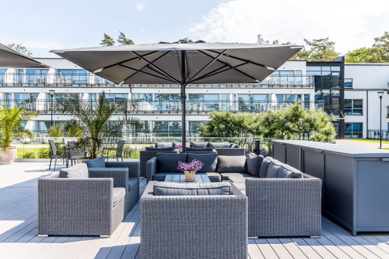 Sittgrupp med parasoll på terrass på innergård.