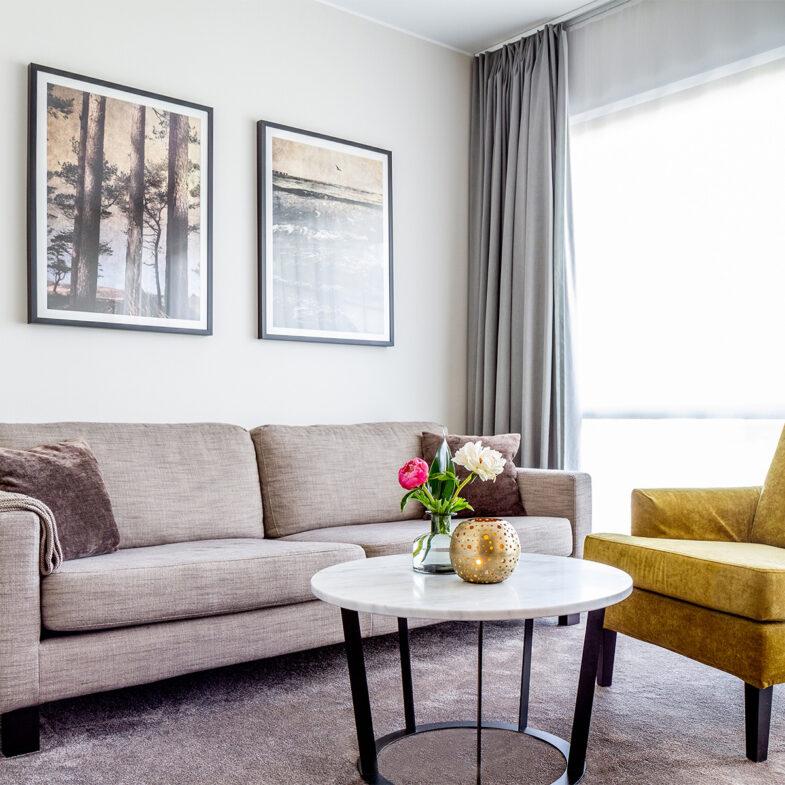 Vardagsrum i hotellrum med soffa och fåtölj