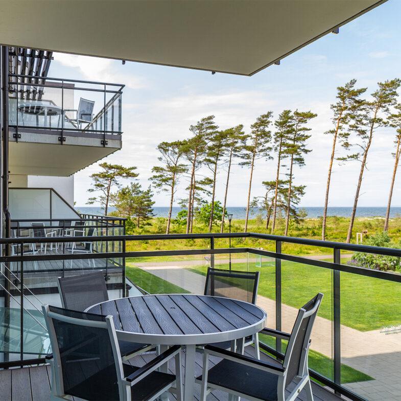 Balkong med utsikt över innergård, träd och hav