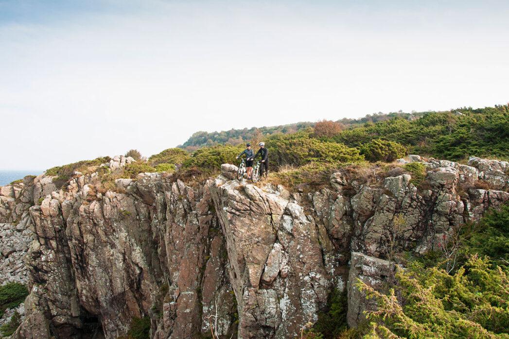 Ett par cyklister på klippa som blickar ner.