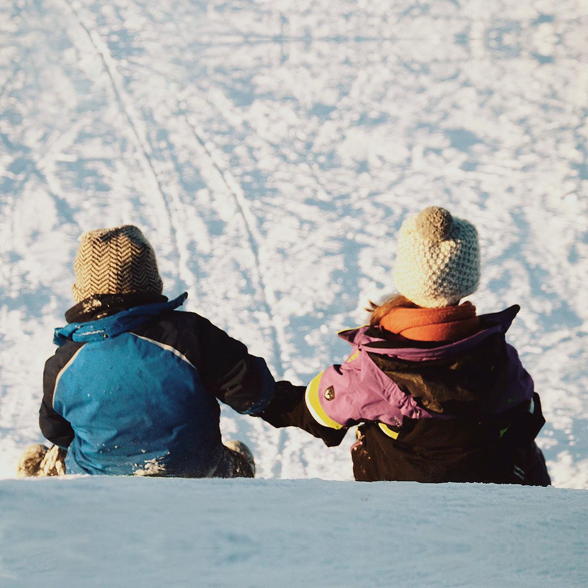 Två barn i skidkläder på väg nerför en skidbacke