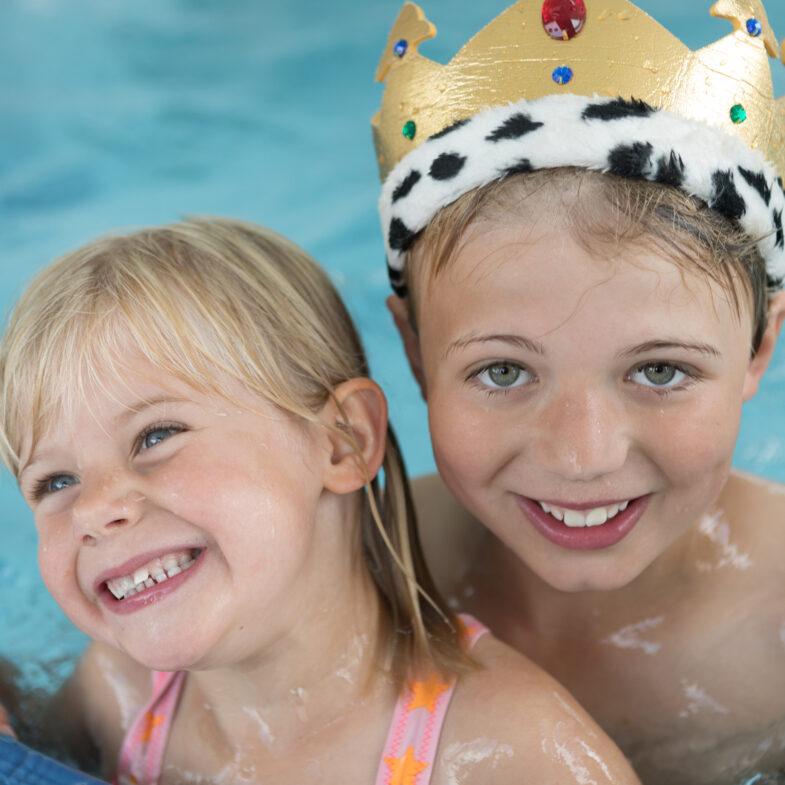 Två glada barn tillsammans i poolen.