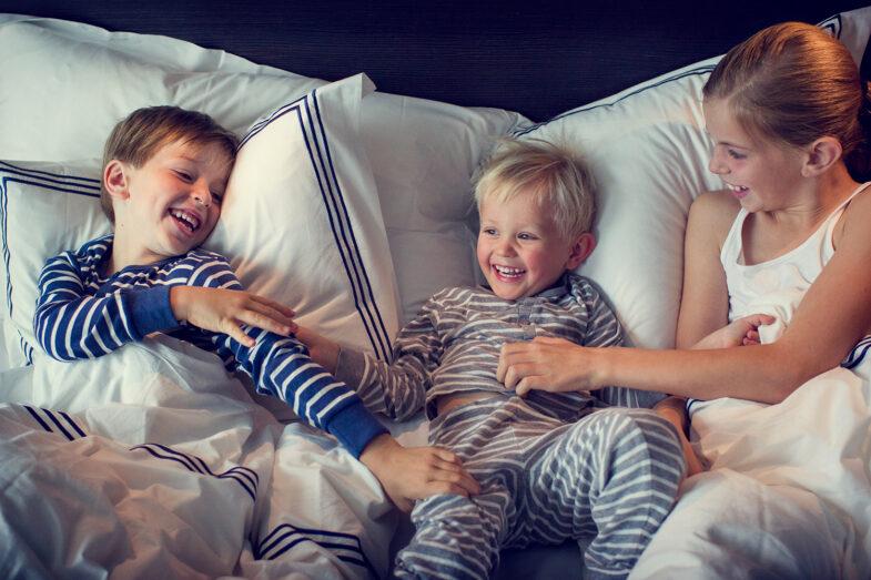 Tre barn i pyjamas i dubbelsäng