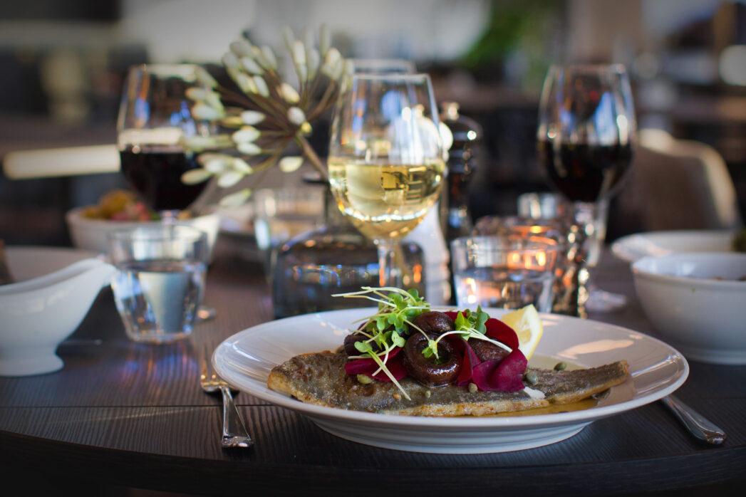 Stekt fisk med grönsaker och ett glas vin
