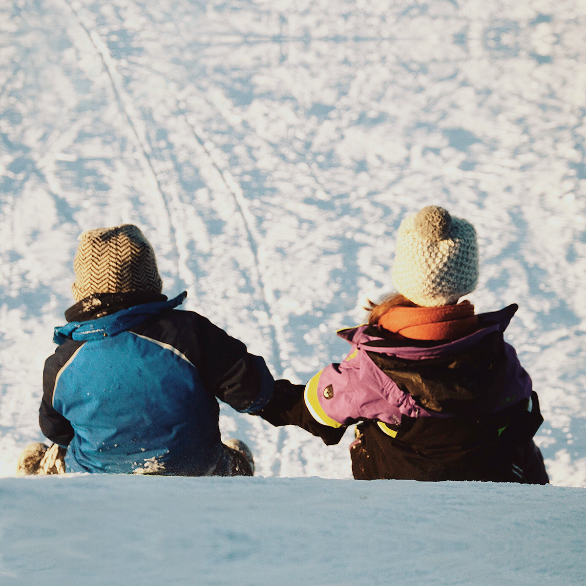 Two kids in winter clothes on their way down a slope on sleighs