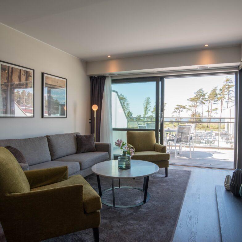 Vardagsrummet och utsikt mot balkongen och havet i svit.